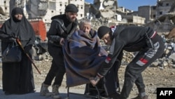 An elderly Syrian man is carried during an evacuation operation of rebel fighters and their families from rebel-held neighborhoods in the embattled city of Aleppo on December 15.