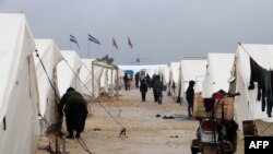 Displaced Syrians walk past tents at the Bab al-Salama camp, set up outside the Syrian city of Azaz on Syria's northern border with Turkey.