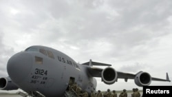 U.S. soldiers board a plane bound for Afghanistan at the U.S. Transit Center at Manas airport.