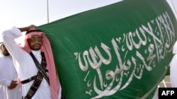 A Saudi policeman in traditional garb holds the Saudi flag