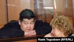 Former Kyrgyz State Committee for National Security agent Aldayar Ismankulov (behind glass) with lawyer Svetlana Murzina in court on June 6