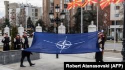 Македонски войници издигат знамето на НАТО по време на официална церемония пред сградата на правителството в Скопие на 12 февруари