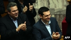 Greek Prime Minister Alexis Tsipras (right) and member of coalition government and Defense Minister Panos Kammenos applaud as the government wins a confidence vote early on February 11.