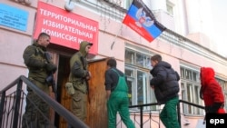 Armed security men guard a polling station during the elections in Donetsk on November 2.