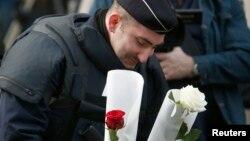 Сотрудник парижской полиции возлагает цветы к месту теракта возле здания концертного зала «Батаклан» в Париже. 14 ноября 2015 года.