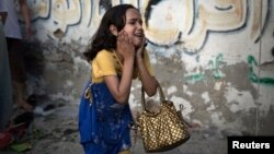 A Palestinian girl reacts at the scene of an explosion that medics said killed eight children and two adults, and wounded 40 others at a public garden in Gaza City on July 28.