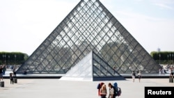 FRANCE - FILE PHOTO: Tourists stand in front of the Louvre Pyramid designed by Chinese-born U.S. Architect Ieoh Ming Pei in Paris, France, September 13, 2016