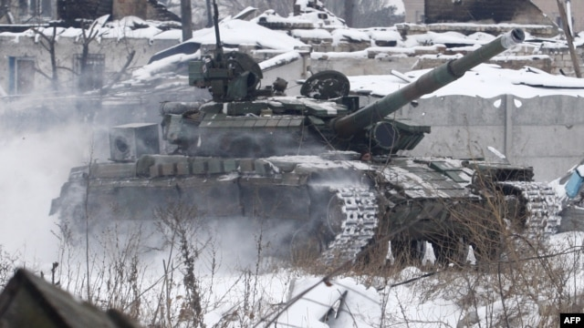 Ukrainian servicemen ride in a tank close to the airport in the eastern city of Donetsk, a facility which has been the site of intense fighting for several weeks.