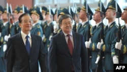 China's Prime Minister Wen Jiabao (left) and his Kyrgyz counterpart review Kyrgyz honor guards at Manas airport in December, 2012.