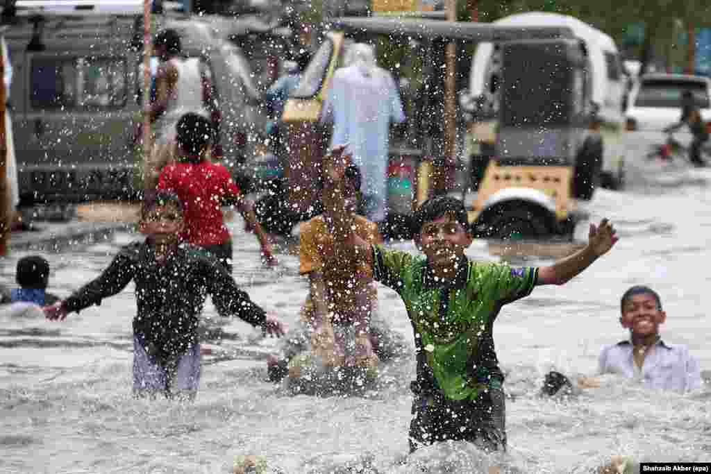 Street children enjoy themselves as the monsoon rains flood the streets of Karachi, Pakistan. (epa/Shahzaib Akber)