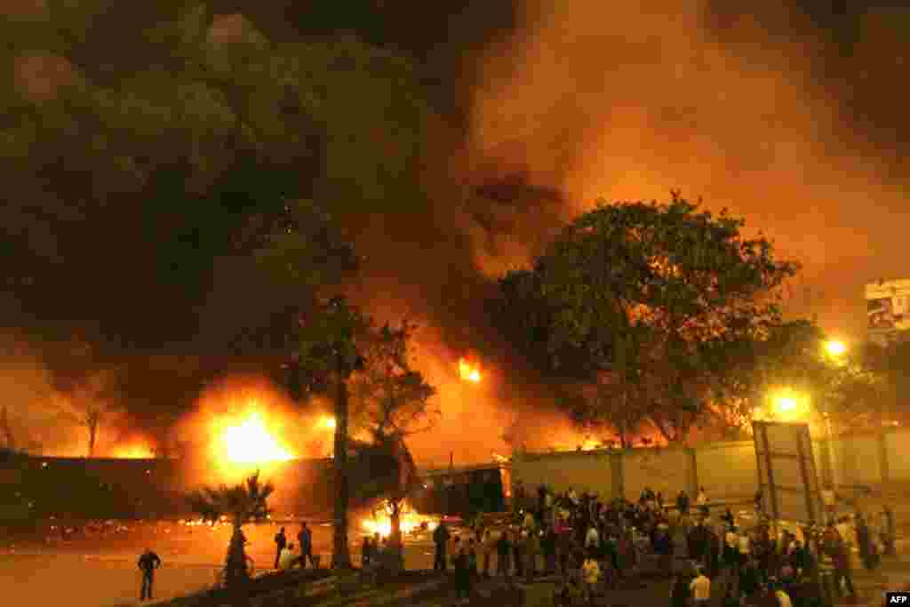 Egyptians gather around the burning headquarters of the ruling National Democratic Party in Cairo on January 28, 2011.