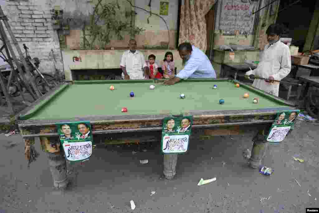 Men play pool in Pakistan on a table decorated with campaign posters. Pakistan's general elections will be held on May 11. (Reuters/Mani Rana)