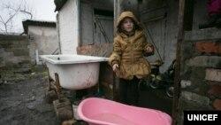 Софии 6 лет. Она стоит в своем дворе в Оленовке Волновахского района Донецкой области (неподконтрольной правительству) возле детской ванночки, в которую семья собирает техническую воду. Когда идет дождь, родители девочки спешат набрать воду в разные сосуды. С начала конфликта вода в дворовом колодце начала горчить. Прежде, чем готовить пищу или пить эту воду, семья вынуждена кипятить ее и давать отстояться некоторое время