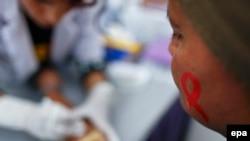 Молодая женщина с рисунком символа борьбы со СПИДом на лице сдаёт анализ крови. Иллюстративное фото.