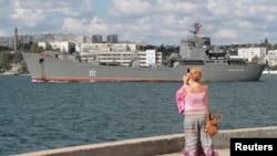 Ресейдің әскери-теңіз кемесін суретке түсіріп тұрған әйел. Севастополь, 6 қыркүйек 2013 жыл. (Көрнекі сурет)