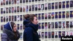 Женщины смотрят на фотографии украинских солдат, погибших в конфликте с пророссийскими сепаратистами. Киев, 25 ноября 2014 года.