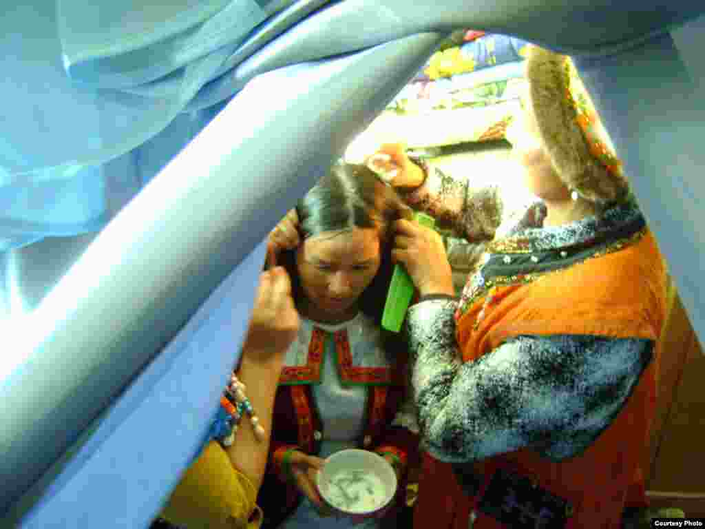 The groom's sisters treat the bride's hair with a mixture of milk and pine needles and arrange her hair into two braids, the style for married women.