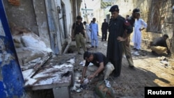 Police collect evidence at the site of the suicide bomb attack in Pabbi on July 26.