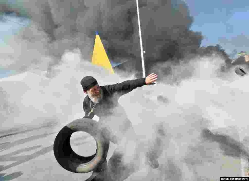 An Orthodox priest throws a tire as activists clash with volunteer servicemen trying to protect municipal workers.