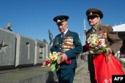 Ветераны Второй мировой, воевавшие в Красной армии, возлагают цветы к памятнику в Риге