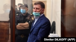 Khabarovsk Governor Sergei Furgal stands inside a defendants' cage during a court hearing in Moscow on July 10.