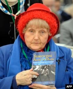 Ева Мозес Кор показывает на фотографию себя и своей сестренки-близнеца на обложке книги об Освенциме.