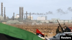 A Kingdom of Libya flag placed in front of a refinery in Ras Lanuf on March 8