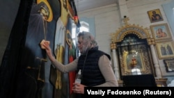Служниця у православній церкві дезінфікує поверхню ікони. Білорусь. Березень 2020 року