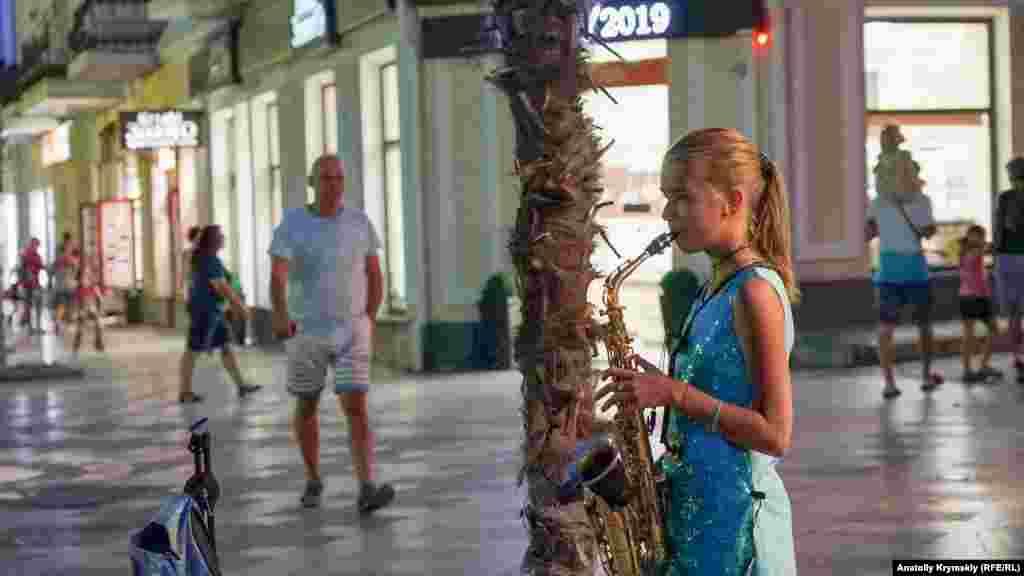 Юную саксофонистку на этом же месте у моря можно было увидеть почти во все летние вечера