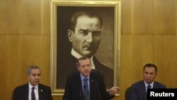 Prime Minister Recep Tayyip Erdogan, flanked by deputies Bulent Arinc (left) and Bekir Bozdag, calls for calm during a news conference in Istanbul on June 3.