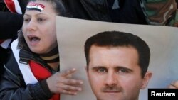 President Bashar al-Assad supporters attend a rally in Damascus on January 20.
