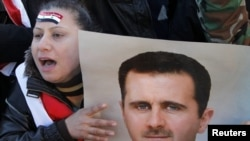 Supporters of Syria's President Assad attend a rally in Damascus on January 20.