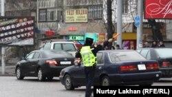 Сотрудник полиции регулирует движение на перекрестке в Алматы. 20 марта 2014 года.
