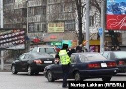 Инспектор дорожной полиции в Алматы регулирует транспортное движение.