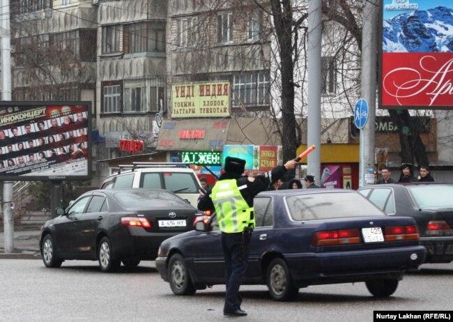Алматыдағы жол жүрісін реттеп тұрған жол полициясы инспекторы.