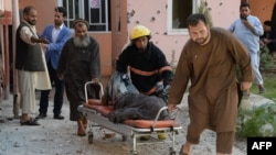 A body is removed from the scene of a suicide attack that targeted the Afghan state television building in Jalalabad in May.