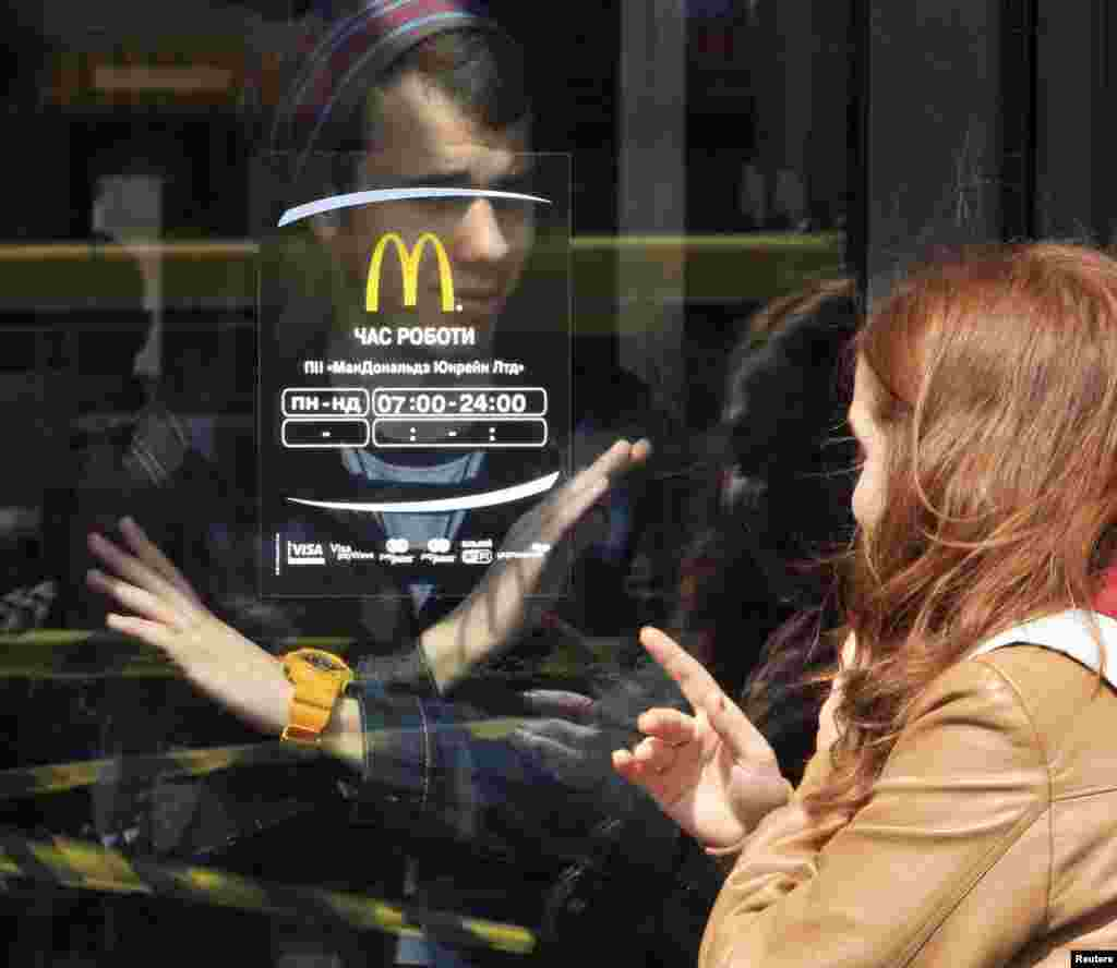 A man signals to a woman that the McDonald's restaurant is closed in the Crimean city of Simferopol. (Reuters)
