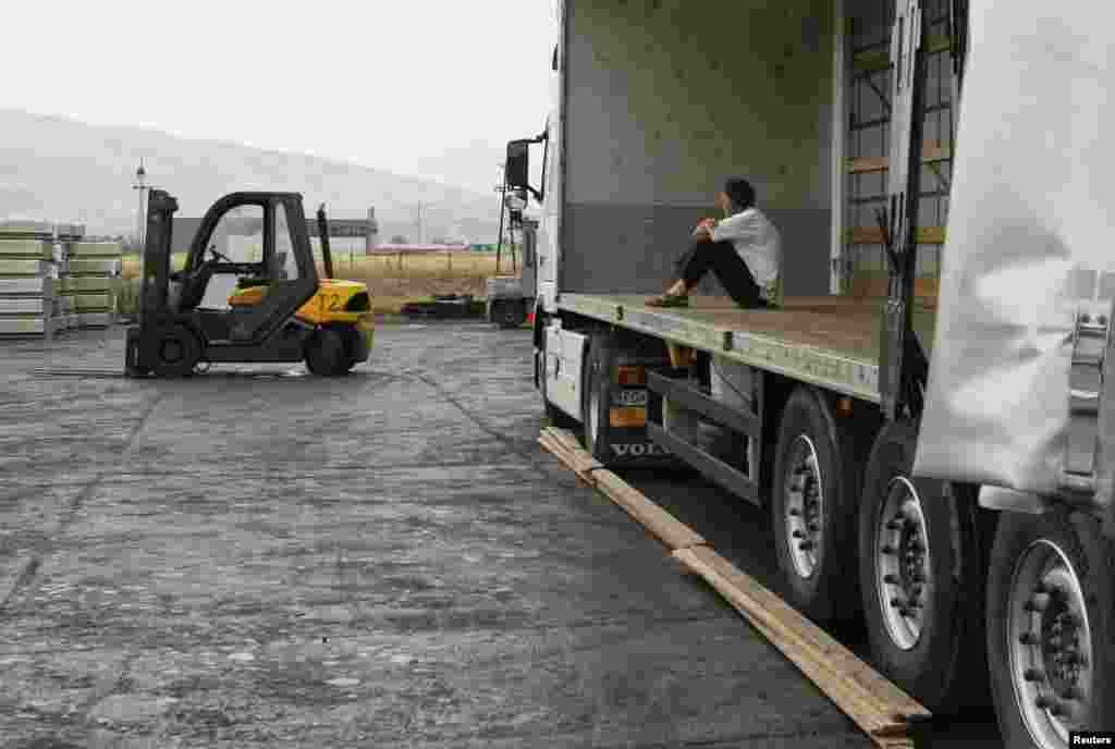 A truck driver waits for products to be loaded.