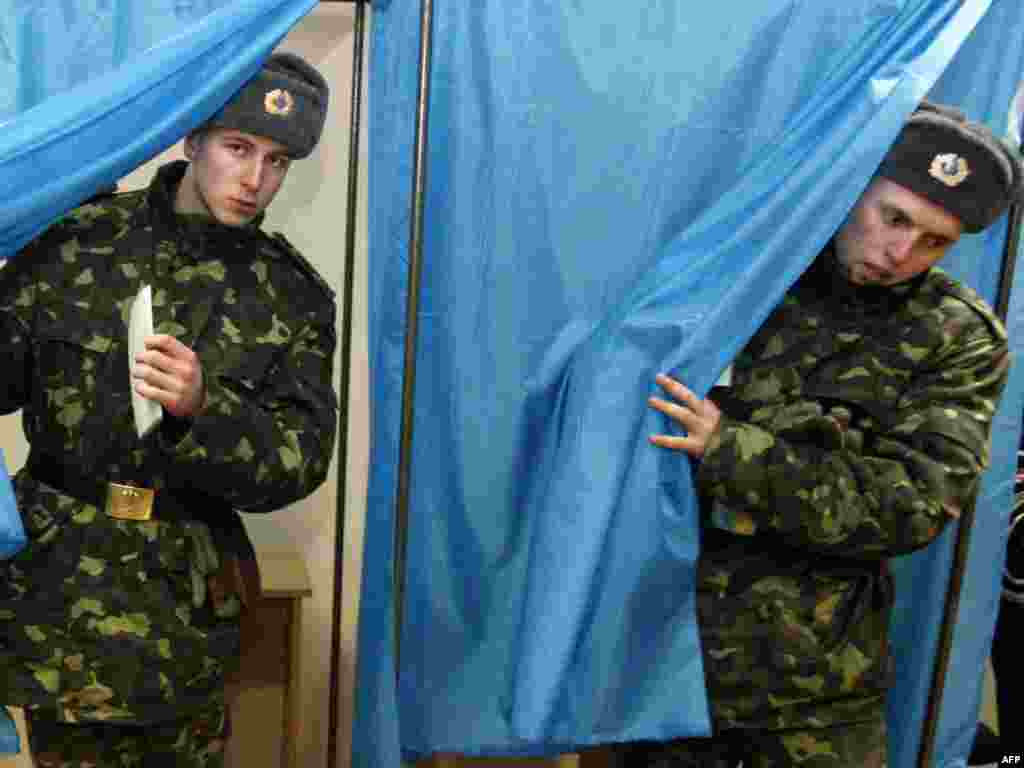 Ukrainian soldiers from the Presidential Regiment exit voting booths at a polling station in the capital.