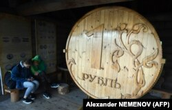 A couple sits next to a huge wooden Russian ruble coin in the center of the Siberian city of Tomsk on September 8.