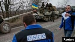 Сотрудники мониторинговой миссии ОБСЕ наблюдают за отводом украинской военной техники. Донецкая область, 26 февраля 2015 года.