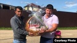 Дилшод Тохиров (слева) принимает подарок от местного жителя.