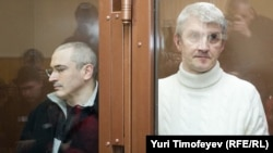 Mikhail Khodorkovsky (left) with Platon Lebedev inside the bullet-proof glass defendents' cage of a Moscow court.