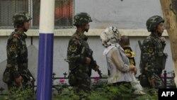 Үрімжі көшелерінде жүрген қытай полицейлері жанынан өтіп бара жатқан балалы әйел. (Көрнекі сурет)