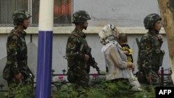 Вооруженные сотрудники китайских силовых структур ведут уйгурскую женщину с ребенком. Урумчи, июль 2010 года.