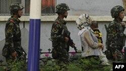 Китайские солдаты сопровождают женщину-мусульманку в городе Урумчи в провинции Синьцзян.