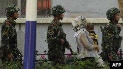 Қарулы қытай жасағы мен бала көтерген ұйғыр әйелі. Үрімжі, шілде, 2010 жыл.
