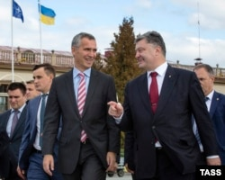 Ukrainian President Petro Poroshenko (right) speaks with NATO Secretary-General Jens Stoltenberg (left) during a welcoming ceremony in Lviv on September 21.