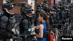 Журналистка пытается завести разговор с офицером полиции, стоящим в оцеплении возле стадиона, где будет проходить съезд Республиканской партии в Кливленде