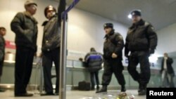 Russian police walk past flowers left in memory of those killed in the blast at Moscow's Domodedovo Airport in January.